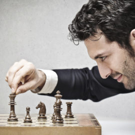 young business man playing chess